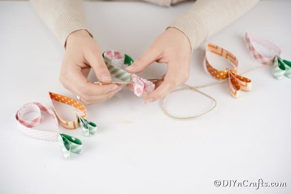 Stringing twine through carrot and egg garland