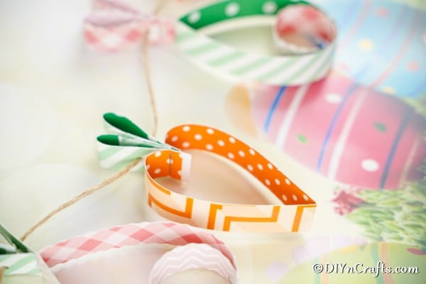 Easter egg and carrot garland on white surface