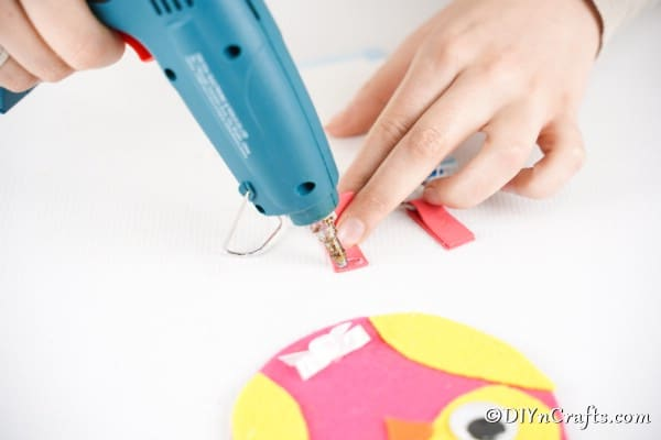 Threading felt leg through keyring and gluing together to create legs
