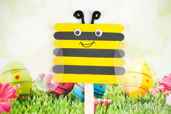 Craft stick bee in front of Easter background