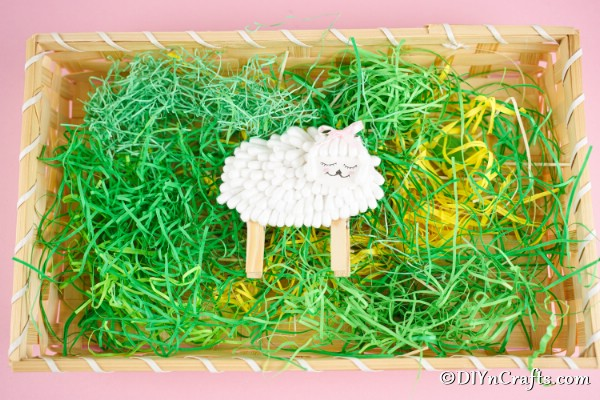 Cotton swab lamb laying in a basket with fake grass