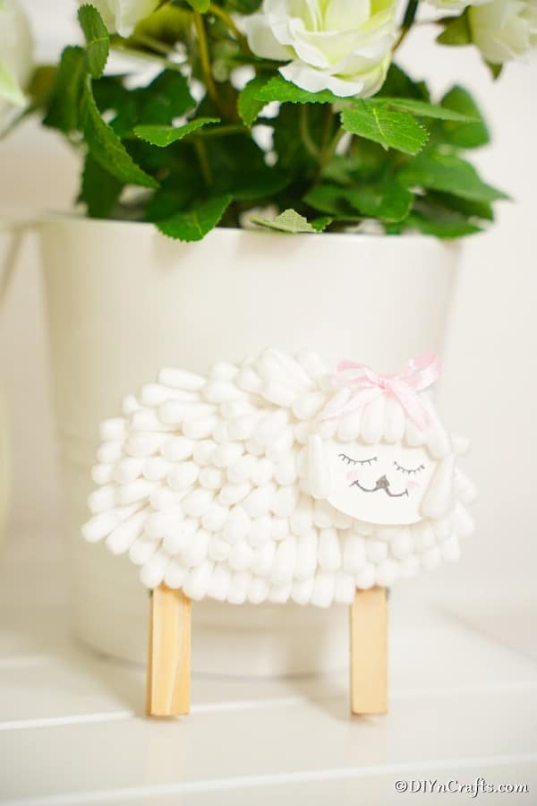 Cotton swab lamb leaned against white flower pot