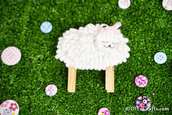 Cotton swab lamb on grass with colorful buttons