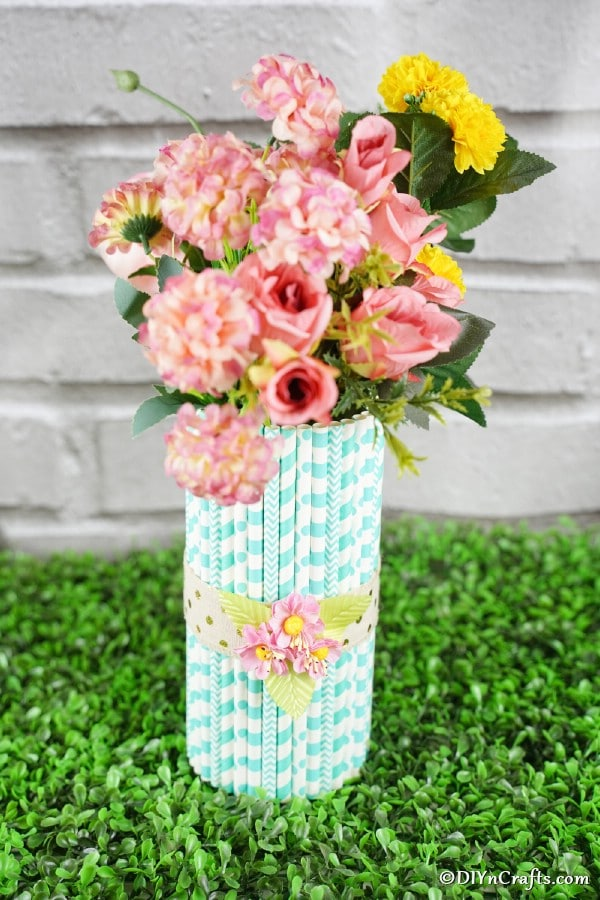 Paper straw vase full of flowers on grass