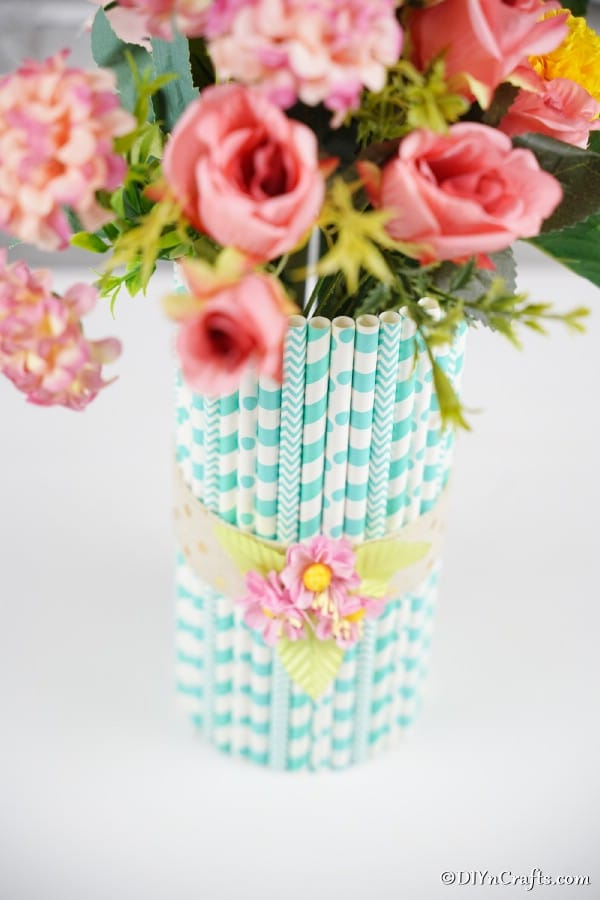 Mason jar vase with blue straws and pink flowers