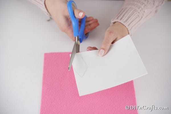 Cutting out bunny ears from white paper