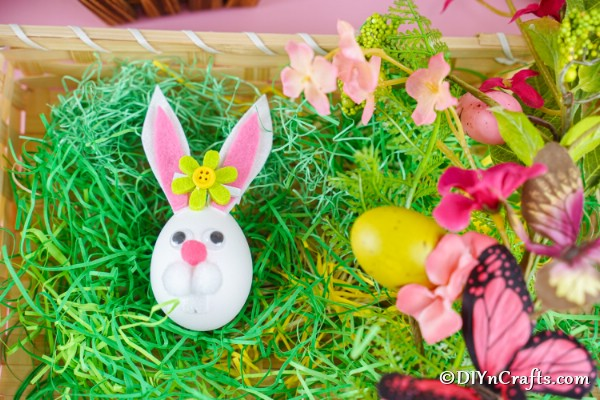 Bunny easter egg in basket with fake grass