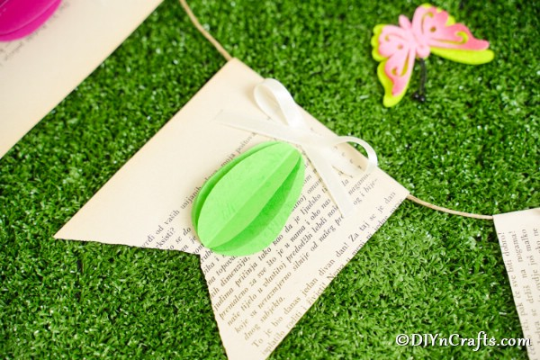 Green 3D egg on old book page banner on grass