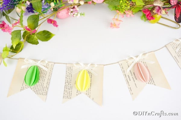 Egg garland laying on white surface with fake flowers
