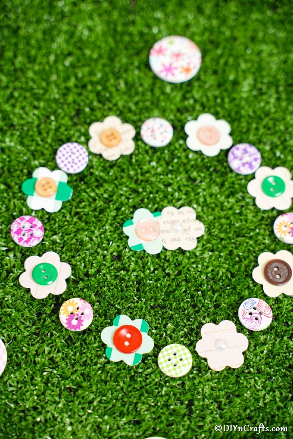 Paper button flowers laying on fake grass