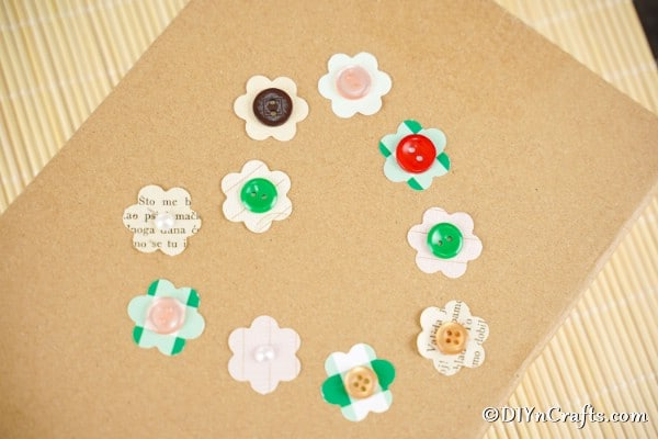 Paper button flowers on a cardboard piece