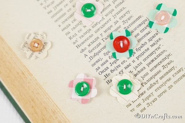 Paper button flowers laying on an open book