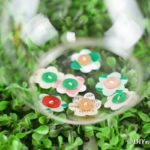 Paper button flowers in a glass jar on grass