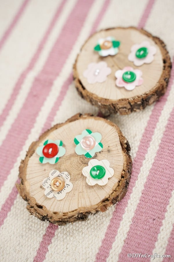 Paper button flowers laying on wood slices