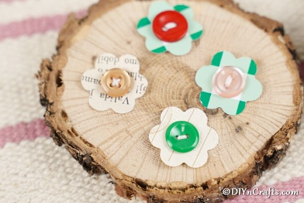 Paper flower buttons on wood slice