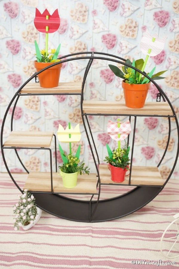 Paper tulips displayed in flower pots on wire shelf