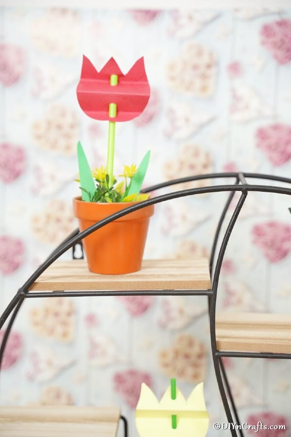 Red paper tulip in a flower pot on wire shelf