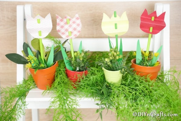 Paper tulips in flower pots on white shelf