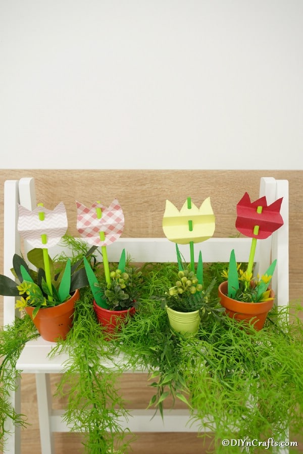Paper tulips in flower pots on shelf with herbs