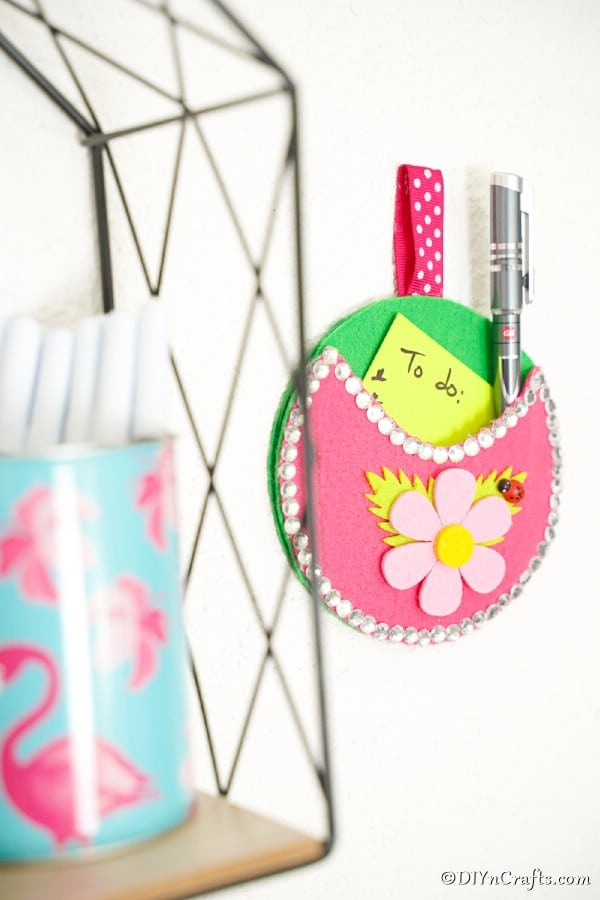 Pocket wall organizer on wall by wire shelf