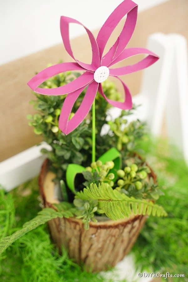 Pink paper roll flower sitting inside a wooden planter