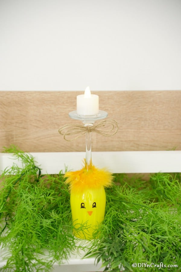 Painted wine glass chicken on fake grass in front of wooden fence