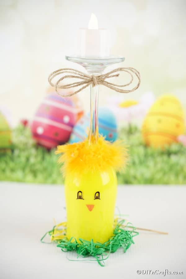 Yellow painted wine glass chicken candle holder on table in front of Easter background