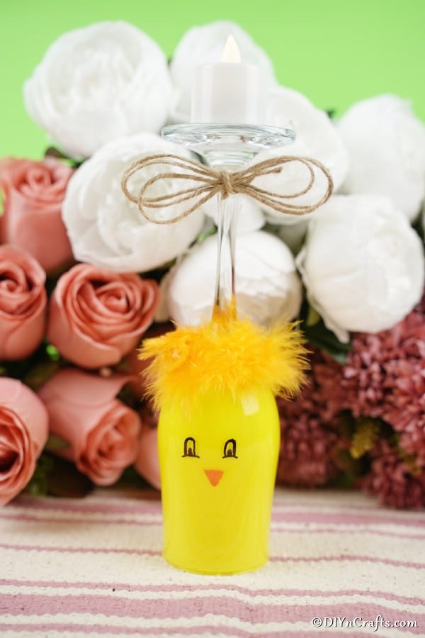 Painted wine glass chicken in front of pink and white roses
