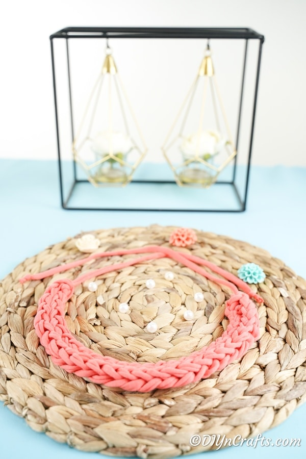 Finger knit pink necklace on woven mat in front of decor