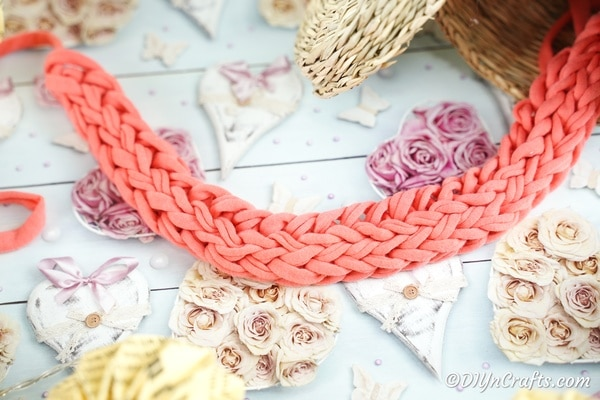 Pink finger knit necklace on floral patterned paper