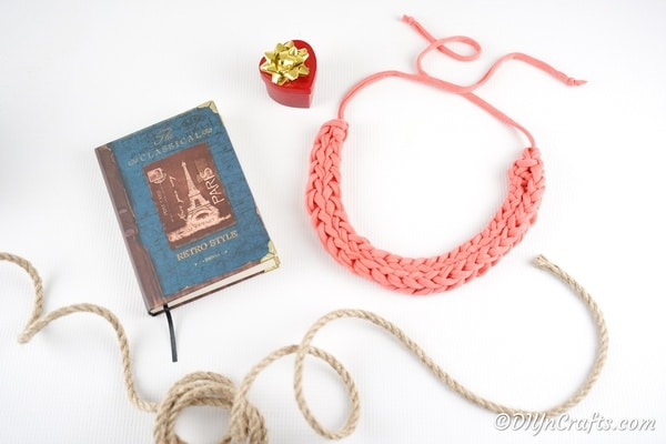 Finger knit necklace on white surface with book