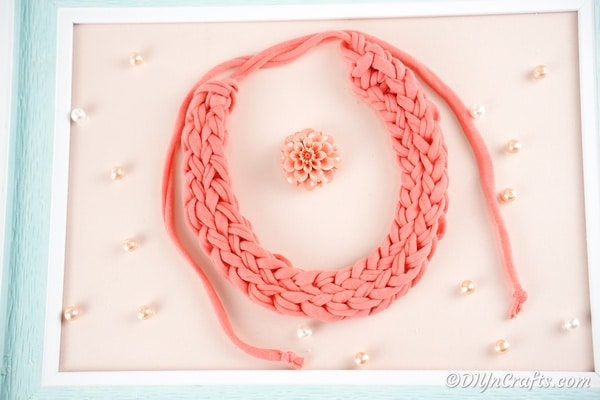 Finger knite necklace on pink surface