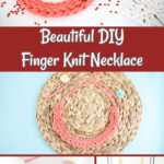 Pink finger knit necklace on woven mat