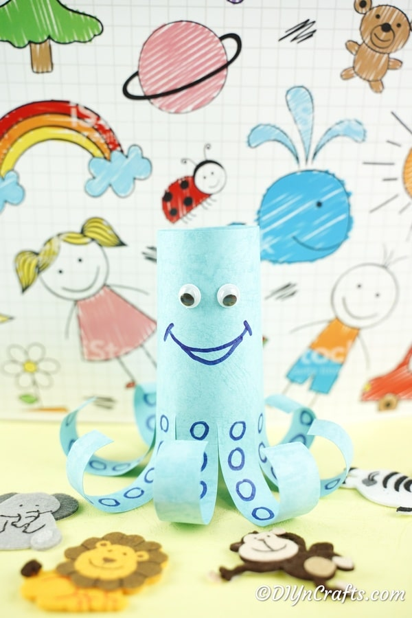 Blue paper octopus in front of colorful paper background