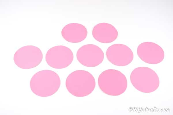 Several pink paper circles on white surface