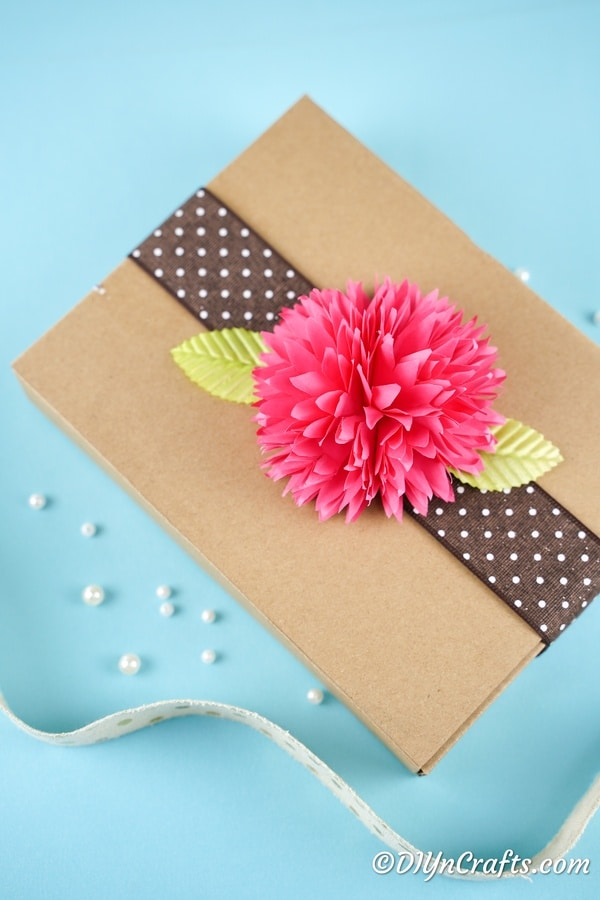 Pink paper flower on top of brown box as gift decor