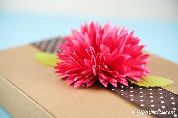 Pink paper flower on top of brown cardboard box