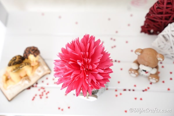 Paper flower on white table with confetti