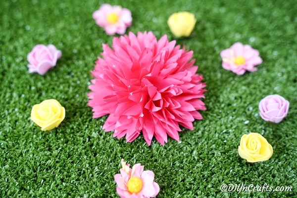 Paper flower on grass surrounded by more flowers