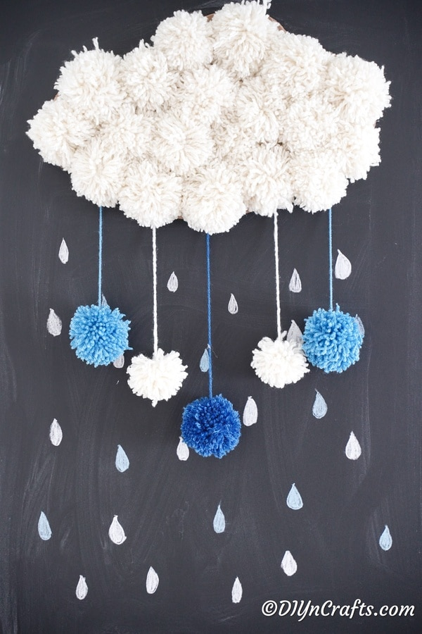 Yarn pom pom cloud on chalkboard