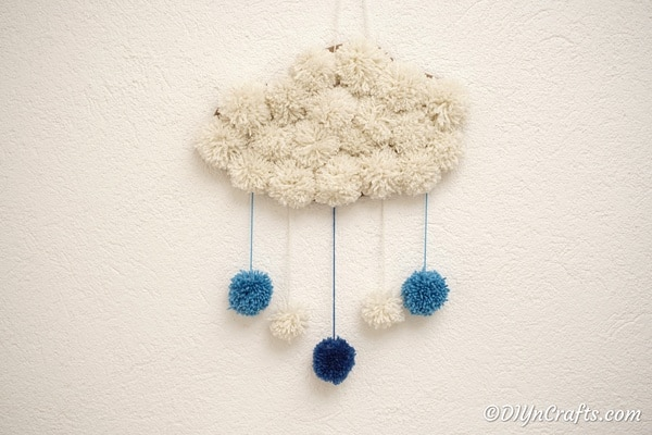 Yarn pom pom cloud on white wall