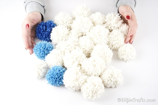Several yarn pom poms on a white table