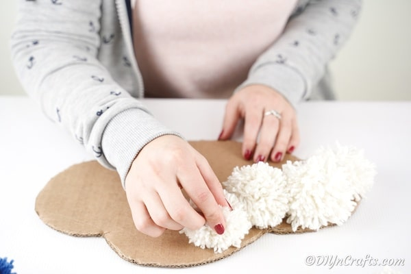 Gluing white pom poms onto cardboard