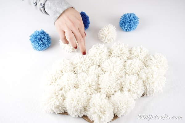 Adding the danging raindrop pom poms to back of cloud