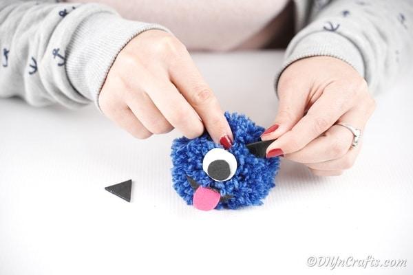 Gluing eyes and ears to blue pom pom