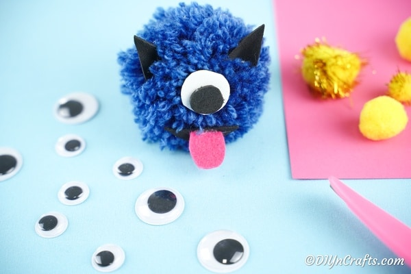 Pom pom monster on blue table with googly eyes