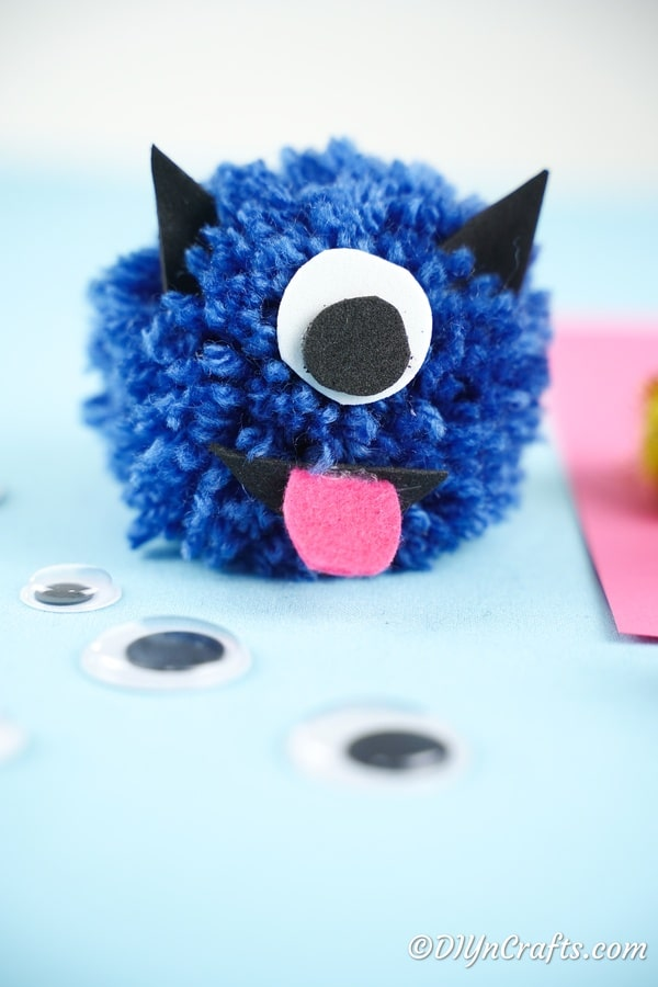 Blue yarn pom pom monster on blue paper