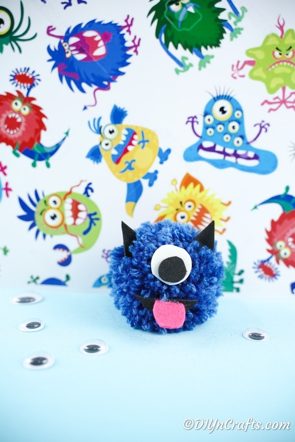 Pom pom monster in front of monster paper