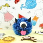Yarn pom pom monster on colorful craft paper