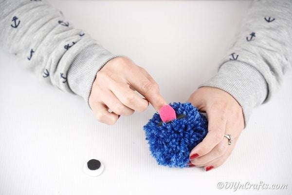 Gluing pink tong to blue pom pom